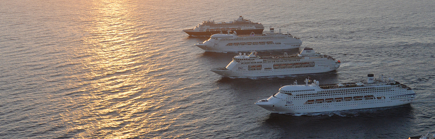 Four cruise ships in a row out at sea with the sun setting