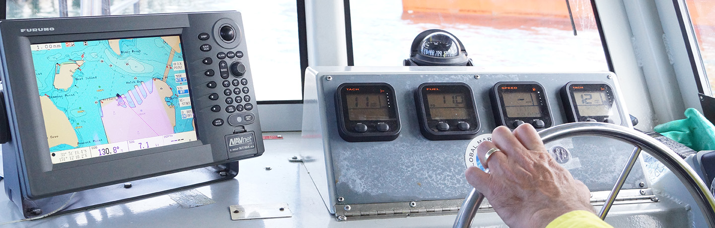 Hands piloting a vessel and following satellite navigation