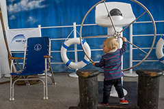 Child in front of vessel stirring wheel at Port Authority community day
