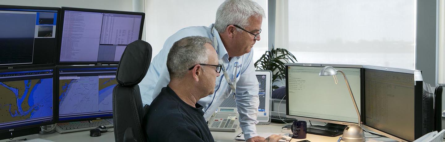 Two Port Authority employees at a desk looking at a computer screen