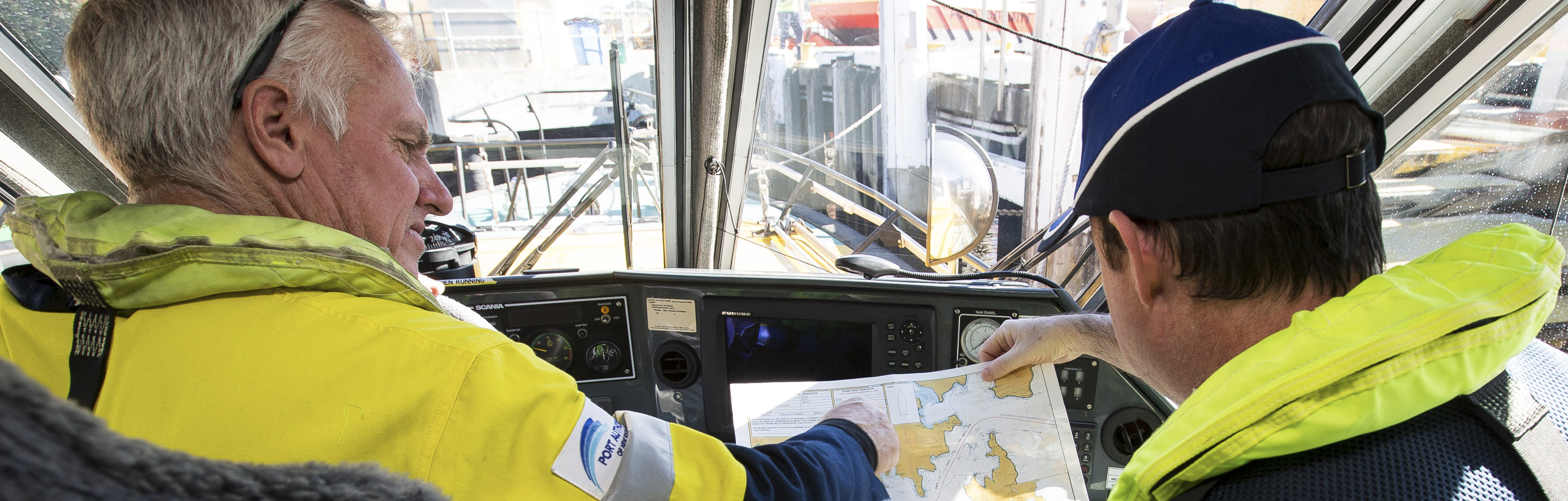 Two Port Authority employees at the helm looking at a map of Sydney Harbour
