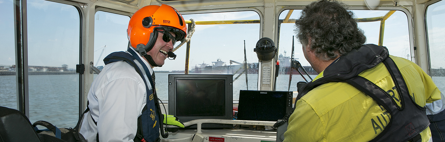 Two Port Authority employees at the helm of a vessel