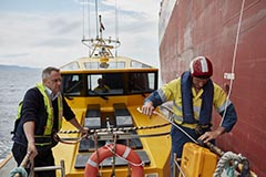 Two Port Authority employees on a pilot vessel ready to take another vessel into port