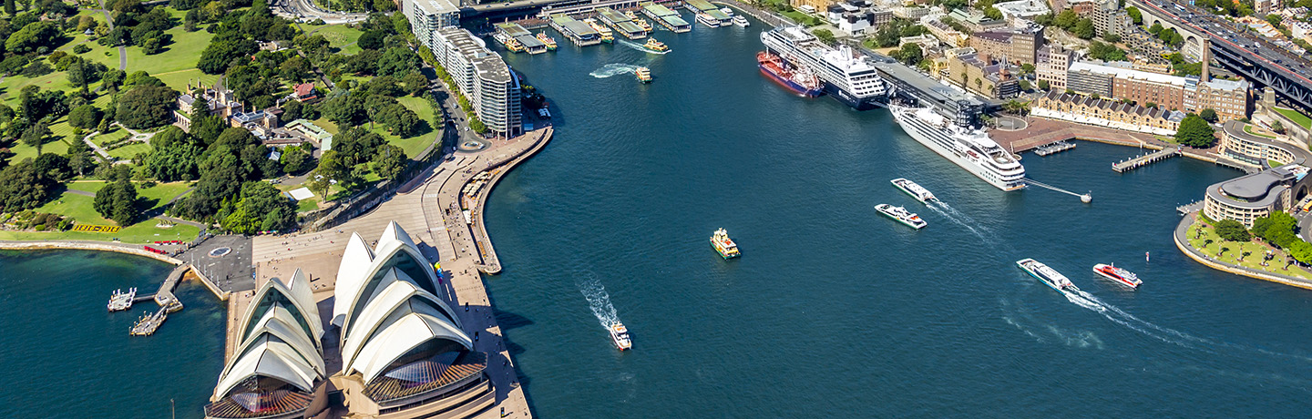 Aerial shot of Sydney Harbour with the Opera house in view, ships entering and exiting the Harbour and two cruise ships double docked at OPT
