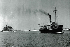 Old photo of the Birubi at sea with Nobby's head in the background