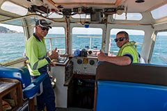 Two pilots on a vessel giving the 'thumbs up' to camera