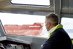 Port Authority employee at the helm of a vessel looking out to sea