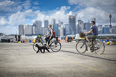 Two people riding their bikes with a dog at Port Authority community day